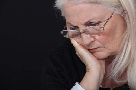 gray haired: grandmother looking concerned against black background