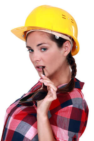 An alluring female construction worker with sunglasses. photo