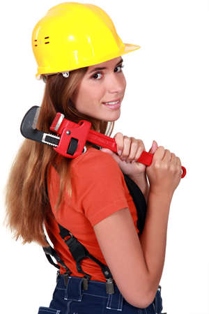 Woman brushing her hair with a pipe wrench photo