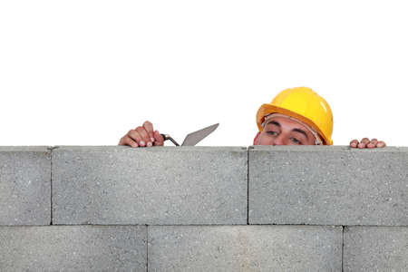 peering: Stonemason peering over a low wall