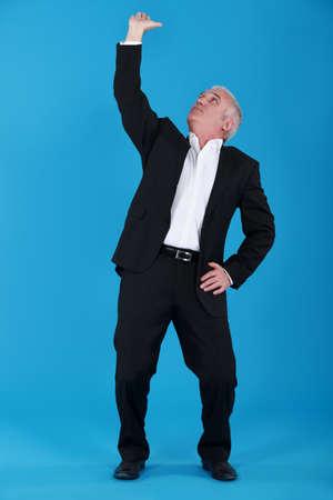 governing: Businessman pushing ceiling
