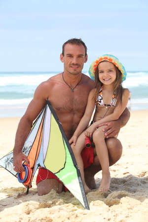 Man on a beach with his daughter and a kite photo