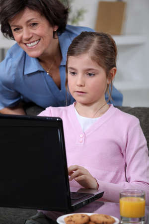 Little girl using laptop at home photo