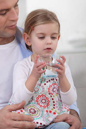 girl drinking water: Father giving his daughter a glass of water to drink Stock Photo