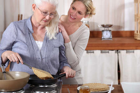 daughter helping her senior mother in the kitchen photo