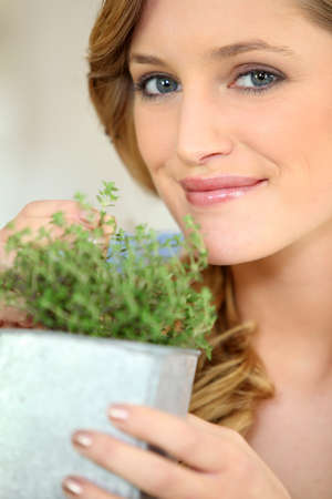 aromatic: Young woman with a pot of thyme Stock Photo