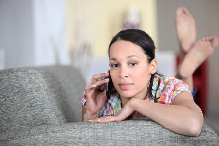 Woman lying on a couch and talking on the phone photo