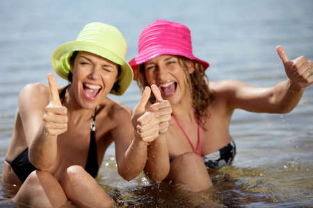 Two female friends at the beach giving thumbs-up photo