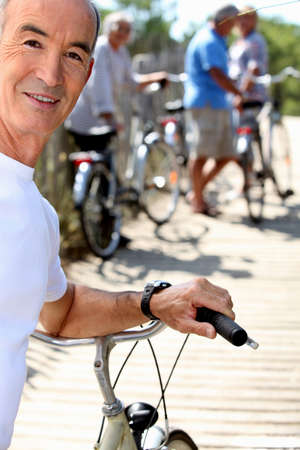 Senior man with a bicycle and his friends in the background photo