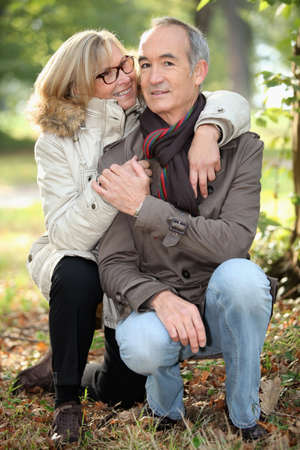 crouch: Mature couple walking in the woods