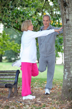 Couple stretching in a park photo
