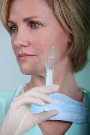 surgical needle: Female nurse holding syringe Stock Photo