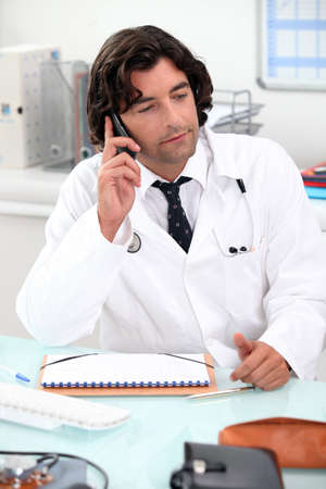 consultant physicians: Doctor using a telephone at a desk