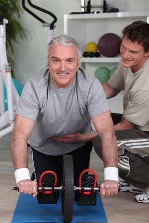 hombres haciendo ejercicio: Hombre de pelo gris con entrenador personal Foto de archivo