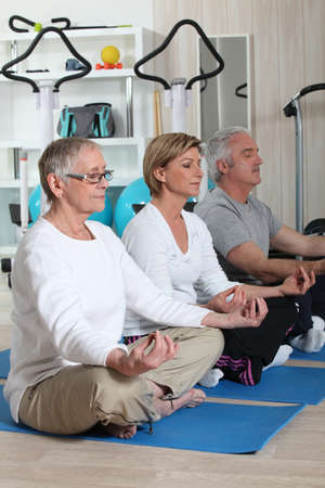 Mature adults doing meditation photo