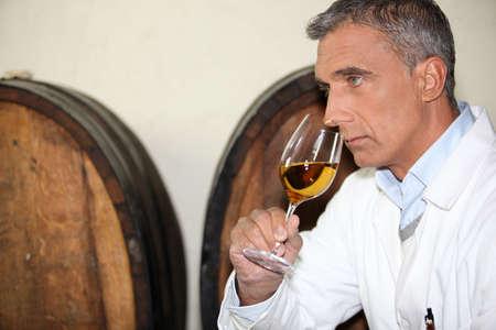 A mature man tasting wine. photo