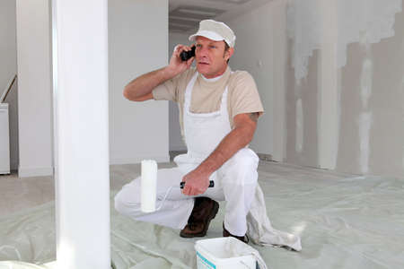Hard-working painter talking to his client photo