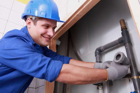 plumbing supply: Young plumber fitting water pipes Stock Photo