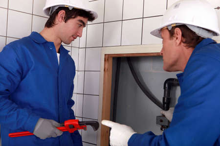 Plumber and his apprentice working together photo