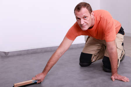 coating: Man smoothing linoleum floor Stock Photo