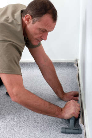 carpet and flooring: Man laying carpet