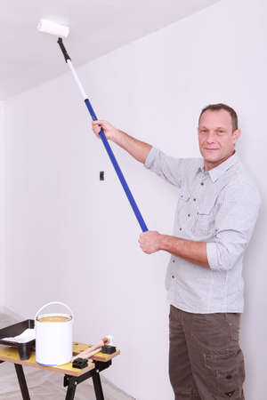 tiresome: Man painting ceiling with roller