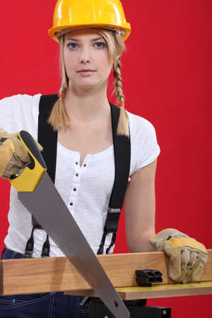 Female carpenter sawing. photo