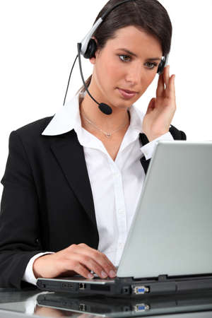 answering call: Woman using laptop computer Stock Photo