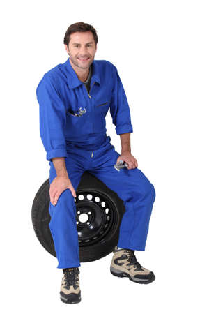 car workshop: mechanic sitting on a tyre Stock Photo