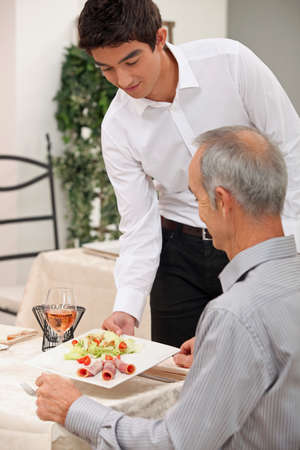 Young waiter serving ham salad