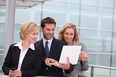 team spirit: Business team looking at a laptop outside a glass building