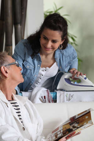 a young woman ironing and talking to an older woman photo