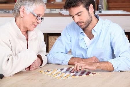 aide à la personne: Jeune homme jouant au jeu avec une femme âgée