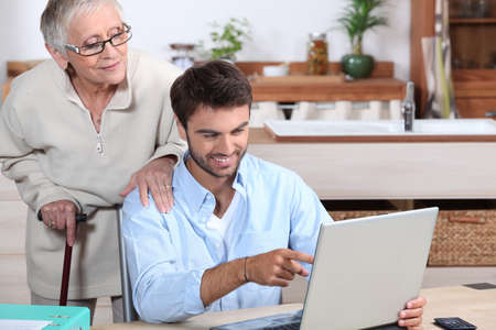 old pc: Man showing old lady how to use computer Stock Photo