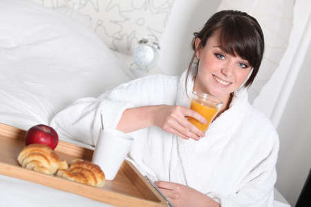 Cheerful girl having breakfast in bed Stock Photo - 11394221