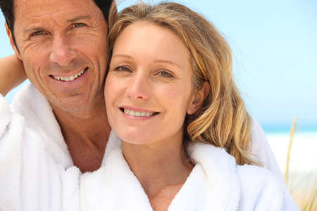 bath gown: tender senior couple near the sea