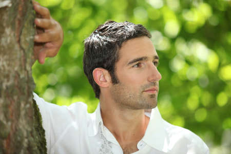 leaning against: Handsome man leaning against a tree in a park Stock Photo