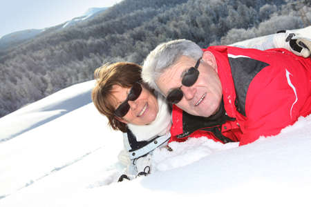 Middle-aged couple skiing photo