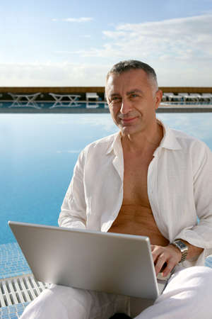 Man sat at edge of pool with laptop photo
