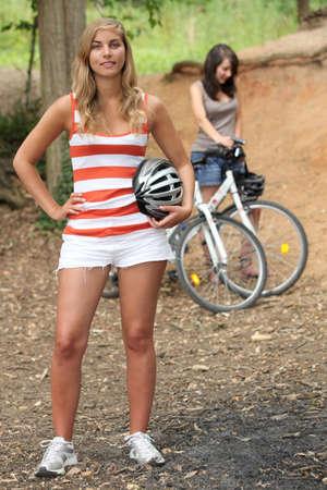 battered woman: two young women reposing near mountain bikes