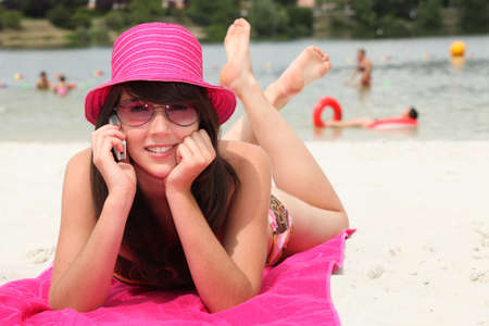 smiling 20 years old Asian girl relaxing on the beach and calling photo
