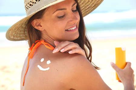 Woman sat on the beach applying sun cream photo
