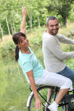 a couple doing bike in the country, the woman is doing airplane with her arms photo