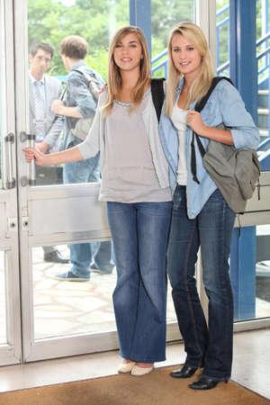 16 17 years girl: Female students opening door Stock Photo