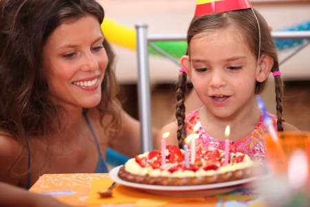 Girl blowing out candles photo