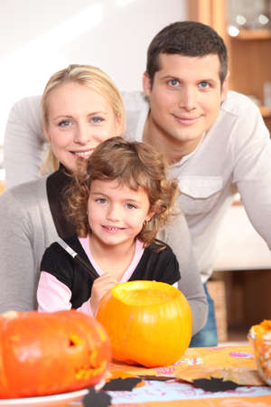 all smiles: Little girl with parents preparing pumpkin for Halloween Stock Photo