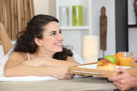 breakfast hotel: Man bringing breakfast to girlfriend Stock Photo