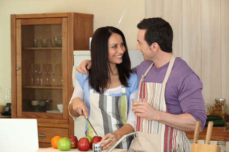 water sink: Couple having fun cooking together
