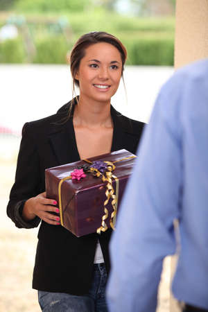 Woman handing man a gift photo