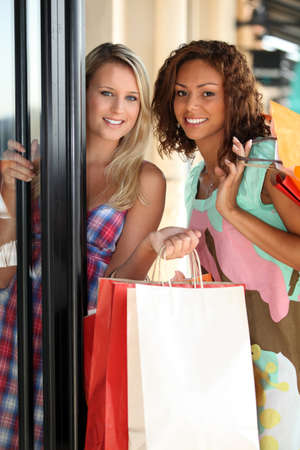 accomplices: portrait of two girls with shopping bags